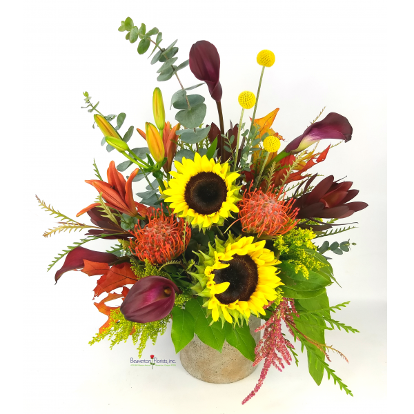"""Beaverton Florists Beaverton - Sarah's choice.  """" When I was asked to make a Fall design, I thought of all my memories while growing up in the countryside.  Fire colored leaves, bright Sunflowers, Sunset color Lilies in a fantastic mix of wild textures.""""    Design of mix Fall colors in a concrete pot."""