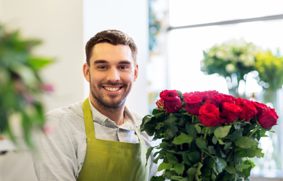 Guy smiling with roses.