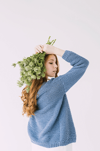 Lady holding small bouquet against hair.
