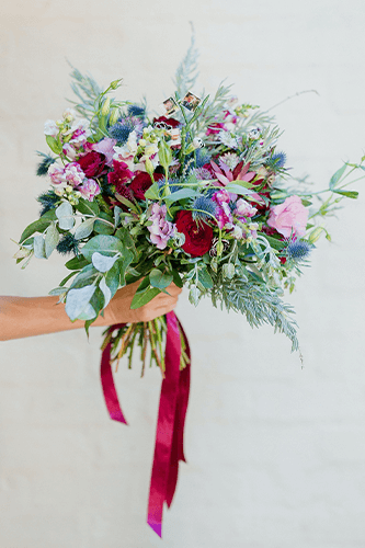 Hand holding large bouquet.