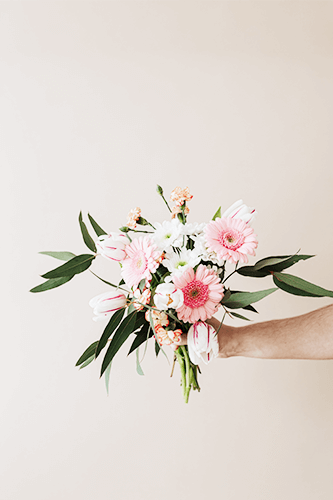 Hand holding small bouquet.