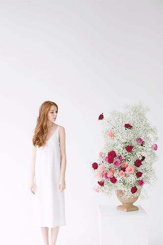 Lady looking at large vase arrangement.