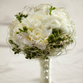 The FTD® Evermore™ Bouquet is a romantic display of modern sophistication. White roses, spray roses, freesia, and hydrangea are accented with green hypericum berries and presented in an elegant gold wire bouquet collar displaying ivory pearls. With the stems wrapped in an ivory satin ribbon accented with domed silver buttons, this bouquet is the perfect companion for your walk down the aisle.  Approx. 9 Inches Diameter