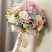 The FTD® Sweet Innocence™ Bouquet blooms with sweet sentiments and endearing charm to get you to look your bridal best on your wedding day. Gorgeous cream roses, pink mini carnations, pink Peruvian Lilies, pink double lisianthus, blue hydrangea and bupleurum are brought together to create an unforgettable bouquet. Tied together with a soft peach satin ribbon accented with pixie pearl pins, this incredible styling culminates in a bow at the base of the bouquet. Approx. 16 x 12