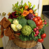 A variety of garden  vegetables combined with fresh flowers in a basket.