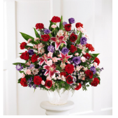 The Floral Tribute Sympathy Arrangement is a bright mix of flowers that include stargazer lilies, carnations, roses, iris and lisianthus.  Appropriate for the traditional memorial or funeral service.