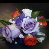 Beautiful rose wristlet adorned with Cosmic Purple ribbon, Lavender, White and orange roses.