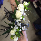 White roses are highlighted by gold pearls black feathers and trim