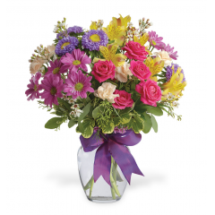Color anyone happy when they receive this bright and sunny flower arrangement - a summery mix of daisy, chrysanthemums, purple asters, pink mini carnations and more, adorned with a cheerful bow. Send one today, and make someone's day!