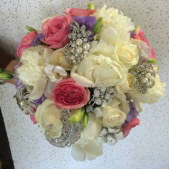 This beautiful clutch bouquet is filled with PNE roses and Lisianthus and includes several approaches as keepsakes