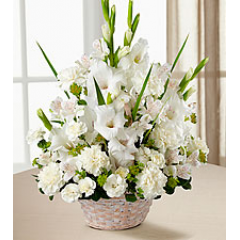 The Eternal Affection™ Arrangement is a peaceful offering of heartfelt sympathy. White gladiolus, Peruvian lilies, carnations, mini carnations and lush greens are beautifully arranged in a round whitewash handled basket to create a beautiful display of soft colors.
