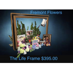 "A Fremont Flowers original! The Life Frame ""frames"" ones life... and is a focal point for any memorial service.  The Urn can rest within the memorabilia that combines favorite items from ones life and combines them with favorite flowers and colors.  A truly touching way to celebrate a life.  The wooden frame to be left at place of service for pickup by Fremont Flowers.  Flowers and memorabilia can be taken to the reception or home after the service.   The Life Frame measures 4.5 ft across."