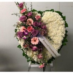 Express your condolences with a solid heart arrangement of carnations accented by a pastel floral cluster. Arranged by a Fremont Flowers designer into a heart standing spray, this is a beautiful arrangement to send to a friend or family member during this difficult time. A variety of sizes are available.  Add a custom printed ribbon at .50 per letter
