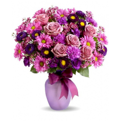 Roses, asters, daisy mums accompany mini carnations and wax flower.  Vase color may vary depending on availability.