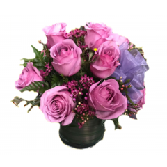 Lavender roses arranged in a glass cube.  This classic bouquet is elegant and fragrant.  Vase will vary, either a clear glass cube or cylindrical vase achieves the same look and feel. Ladies love colors other than the traditional red....so give her what she loves!
