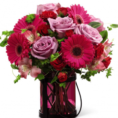 this mixed flower bouquet is set to send sweet wishes with gorgeous grace. Lavender roses, hot pink Peruvian Lilies, fuchsia gerbera daisies, red spray roses and lush greens are brought together to create a perfectly pink presentation. Arranged in a pink glass lantern inspired vase that can be used as a candle holder after the original offering of flowers fades, this mixed flower bouquet will make an excellent birthday, thank you, or congratulations gift.