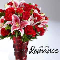 "The Lasting Romance® Bouquet is ready to make your special someone's heart skip a beat!  Stunning Stargazer Lilies are set to catch the eye with their soft fragrance and fuchsia and white bi-colored petals, arranged amongst rich red roses, red carnations, and red mini carnations with lush green accents. The Vase shown is not the vase that this arrangement will come delivered in, rather a red ginger jar style vase.     this gorgeous flower bouquet is the perfect way to express your heart's every wish. approx. 17""H x 15""W."