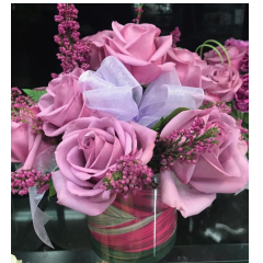 Lavender roses arranged in a glass cube.  This classic bouquet is elegant and fragrant.  Vase will vary, either a clear glass cube or cylindrical vase achieves the same look and feel. Studies indicate that women prefer  colors other than the traditional red rose....so give her what she loves!  This bouquet is easy to transport should it be a gift sent to a workplace.