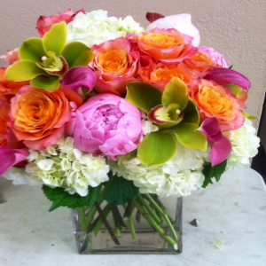 A plethora of flowers including hydrangea, Peonies, (when in season) orchids and roses combine in a elegant glass cube.  A very tasteful gift.  (Substitutions will be necessary when seasonal varieties are not available)