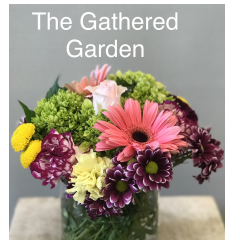 We bring you the Gathered Garden.  This design features Gerbera daisies, hydrangea, a rose, hypericum and carnations along with mums all arranged in a glass container.