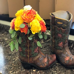 A large resin cowboy boot filled with roses. After the roses have gone, it's special top fits on and it can be used as a waste pale