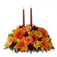 Fall is all about coming together and making memories with one another. The Bright Autumn Centerpiece helps make those precious moments even more special. With red roses, peach Asiatic lilies and red carnations and bronze cushion poms embracing 2 taper candles, this centerpiece is a beautiful gift for every Autumn occasion.