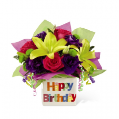 "They will know that a good time is in store when this bright bouquet makes its appearance at any birthday celebration. Birthday joy seems to burst from a bright and beautiful ceramic vase that bears the festive look of a gift wrapped present. The colorful flowers include roses, lilies, stock and carnations...simply the best way to say ""Happy Birthday""!"