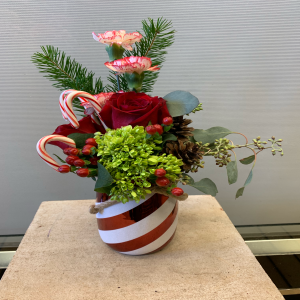 The mason jar Christmas bouquet comes in a glass candycane striped mason jar with real candy canes and other fresh florals.