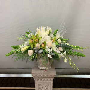 All white with hints of green, includes white roses, hydrangea, orchids, bells of Ireland, Lisianthus