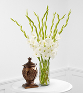 The At Peace™ Bouquet is an elegant and sophisticated symbol of sweet serenity. Brilliant white gladiolus are arranged in a clear glass cylinder vase to create a lovely way to convey your deepest sympathies for their loss.