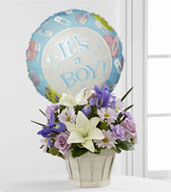 "The Boys Are Best!™ Bouquet is blooming with sweet love to congratulate the new family on their darling baby boy! Lavender roses, blue iris, lavender carnations, lavender daisies, white Asiatic lilies and lush greens are beautifully arranged in a round whitewash woodchip basket. Presented with a Mylar balloon declaring, ""It's a Boy!"" this incredible flower arrangement is the perfect welcome for their new addition."