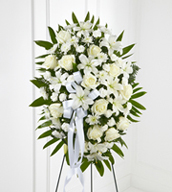 The Exquisite Tribute™ Standing Spray is an elegant display of sweet serenity. White roses, Asiatic lilies, chrysanthemums and mini carnations are artfully arranged amongst emerald palm fronds and lush greens. Accented by white satin ribbon and standing on a wire easel, this standing spray is an outstanding way to honor the life of your loved one.