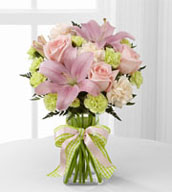 The Girl Power™ Bouquet brings together roses and Asiatic lilies to send your sweetest sentiments and offer your congratulations on the birth of their new baby girl! Pink roses, pink Asiatic lilies, pale peach carnations, pale green mini carnations and lush greens are exquisitely arranged in a clear glass gathered square vase. Accented with a pink satin ribbon, this flower bouquet creates a wonderful way to send your warmest wishes for the adventure of parenthood ahead.