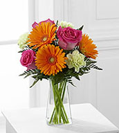 The Pure Bliss™ Bouquet is a blooming expression of happiness and joy set to brighten any day! Hot pink roses, orange gerbera daisies, light green carnations and lush greens are perfectly arranged in a clear gathered square glass vase to send a warm and cheerful sentiment to your special recipient.