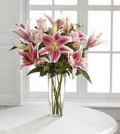 Speak from your heart to theirs with a collection of pink vibrant blooms. Pale pink roses collaborate with the magic of Stargazer lilies displaying their fragrant fuchsia petals amidst waxflower accents. Beautifully arranged  in a clear square tapered glass vase, this bouquet sends your warmest sentiments with glamour and grace.