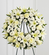 The Treasured Tribute™ Wreath offers peaceful wishes of heartfelt sympathy with each delicate bloom. Bright white roses, Asiatic lilies, mini carnations and cushion poms are beautifully arranged to form an elegant accented with lush and vibrant greens. Displayed on a wire easel, this gorgeous tribute is a wonderful symbol of eternal life and sweet serenity. Approximately 22 inches in diameter.