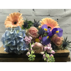 A custom design of soft pastel blossoms offers a subtle touch of color. If you have a preference of low/compact style or a tall & airy design please indicate in special instructions.