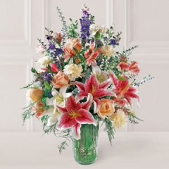 Pink Stargazer Lilies And Pink Roses, A-Swirl With Pink & White Blossoms, Are Gracefully Arranged In A Elegant Glass Vase.