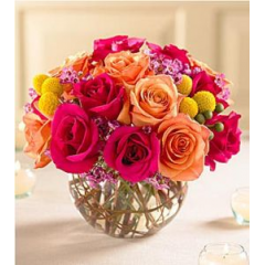 Vibrant Colored Roses Burst From A Glass Bowl. Hot Pink, Orange And Two-Toned Orange Arranged With Golden Craspedia And Deep Pink Wax Flower.