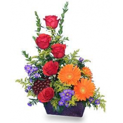 """A tasteful design of red roses, gerbera daisies and other colorful flowers designed in a lovely metal dish…a great way to say """"job well done'!"""