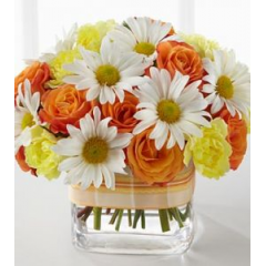 A smart combination of delicate daisies, spray roses and carnations in a sweet cube vase, perfect for a smaller space.