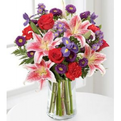 Oriental lilies are always a favorite but you can't miss when you add red roses, iris, asters and carnation in a clear cyinder vase.  Stunning!