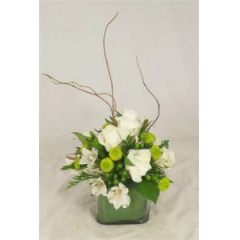 This Contemporary Clear Cube Vase Holds An Array Of Roses, Alstromeria, Green Kermits And Hypericum Berry.