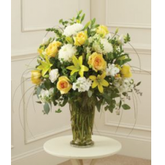 A Beautiful Combination Of Of Yellow Roses & Lilies Arranged With White Stock,Snaps And Mums. This is a welcome gift for the family.