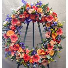 "A beautiful 24"" wreath designed with peach, orange & blue tones that will show your condolences   colors will vary"
