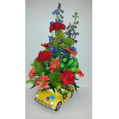 Vibrant fresh flowers create this fun arrangement for dad in a cute keepsake 'bug' container.