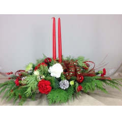 Fresh green centerpiece with ornaments, carnations, pine cones and tapered candles