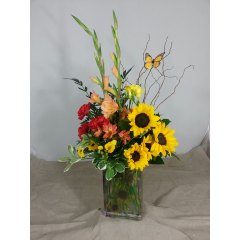 MOM WOULD ENJOY THIS CLEAR RECTANGLE VASE THAT IS DESIGNED WITH GLADIOLUS, SUNFLOWERS, ALSTROMERIA AND ACCENTED WITH A BUTTERFLY
