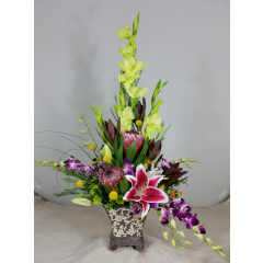 Our very own Tropical Sensation...a perfect mix of lime green glads; pink mink protea; stargazer lilies and dendrobium orchids...the perfect reminder of the Islands! Colors of flowers may vary according to stock on hand.