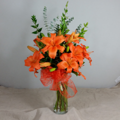 A tall glass cylinder vase holds these cheery, colorful lilies.   Adorned with french wired ribbon, what a striking display!